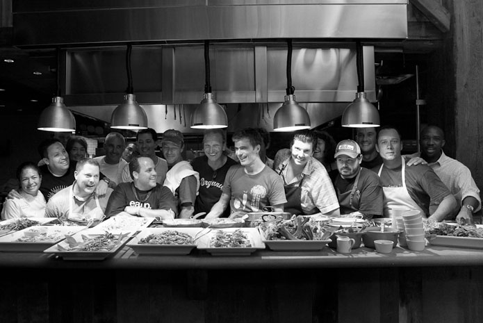 Chefs from a previous JBH Boot Camp enjoy a lighthearted collaborative dinner together.